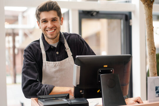 Smiling young man in apron standing at the cash register