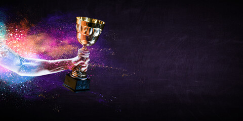 Hand holding up a gold trophy cup against dark background