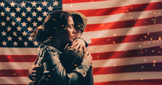 Independence day, memorial Day. A woman embraces a soldier. Couple on the background of the American flag with sparks. Copy space. The concept of American national holidays and patriotism