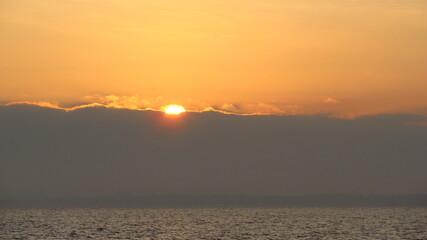 Słońce wschodzi zza chmury nad morzem