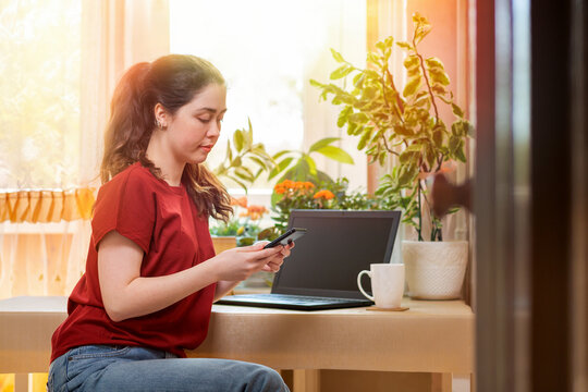 Freelance.A young beautiful woman uses a smartphone. Home decor, the sun outside the window, on the table laptop and a Cup of tea. The concept of quarantine, self-isolation and remote work
