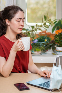 A young woman holding a Cup of tea and working at a laptop, on which hangs a medical mask, and next to the table is a smartphone. Concept of self-isolation and protection from coronovirus