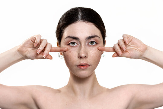Beauty and skin care. Portrait of a young beautiful Caucasian woman pointing her fingers under the eye area. White background. The concept of lifting procedures against the first signs of skin aging