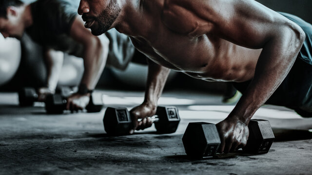 Muscular man weight training with dumbbells wallpaper