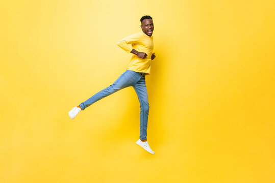 Young happy excited African man jumping, raising one leg and clenching hands on isolated yellow studio background