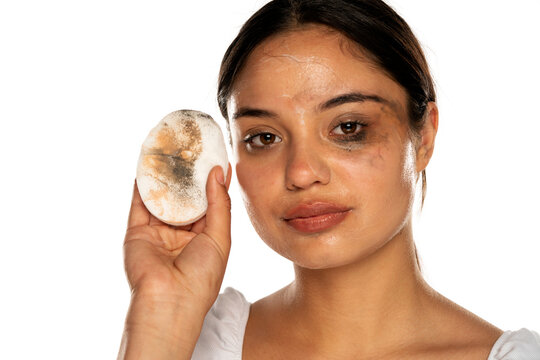a young woman shows a dirty cotton pad as she wipes her face