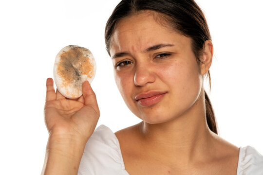 a young disgusted woman shows a dirty cotton pad as she wipes her face
