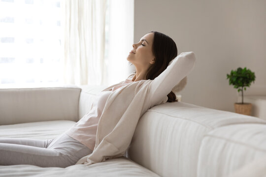 Happy millennial woman relaxing on sofa, breathing cool air from conditioner, enjoying comfortable climate in ventilated living room, meditating with closed eyes. Comfort at home, conditioning concept