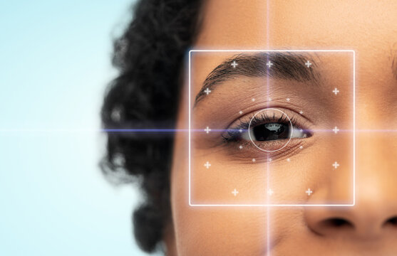 vision correction, laser eye surgery and health concept - close up of young african american woman face over blue background