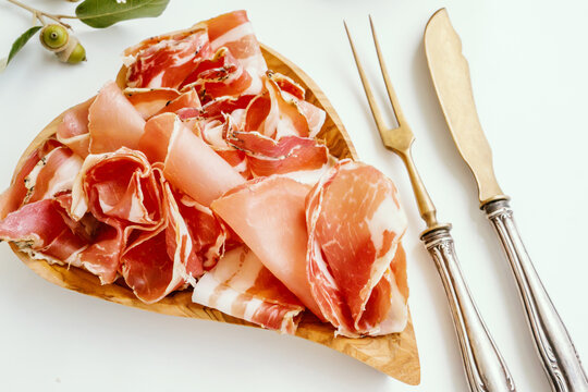 thin slices of jamon are laid out on a wooden board made of olive wood. Close-up of a thin slice of Iberian ham ham on a wooden olive plate