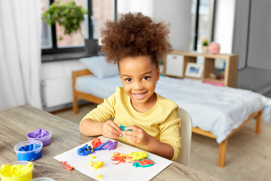 childhood, creativity and hobby concept - little african american girl with modeling clay playing at home