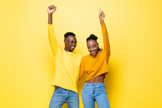 Cheerful smiling young African American couple raising hands up in the air on yellow isolated studio background