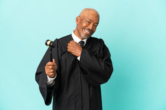 Judge senior man isolated on blue background celebrating a victory