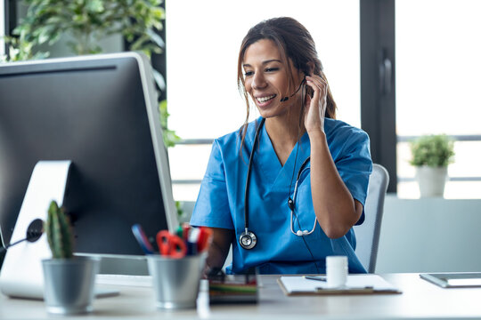 Female doctor talking with earphone while explaining medical treatment to patient through a video call with computer in the consultation.