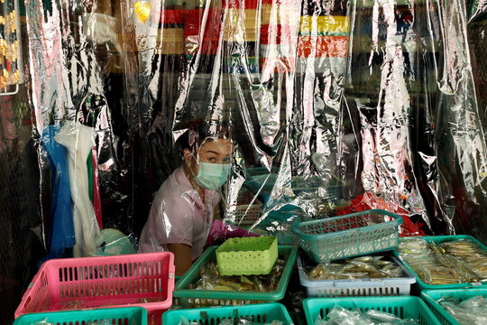 A shopkeeper is seen behind a protecting plastic curtain in Bangkok