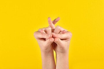 Children's hand showing an ostrich collected from fingers on yellow background. Figures from hands. Fine motor skills. Developing activities