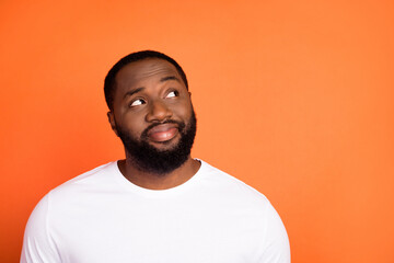 Photo of attractive happy young afro american man look empty space dream isolated on orange color background Wall mural