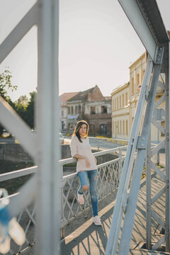 Vertical shot of a beautiful white Caucasian girl leaned on a fence