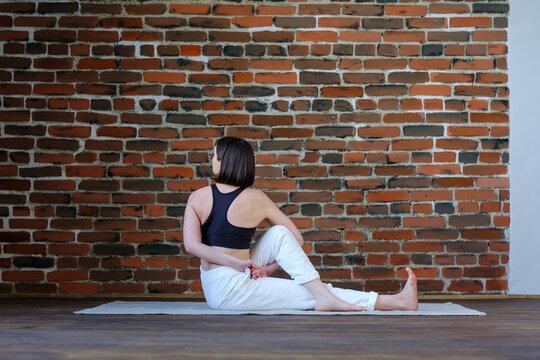 Young yogi woman practicing yoga, doing Marichyasana exercise, wearing sportswear, white pants black top, indoor full length, brickwork wall in yoga studio. The pose of the sage Marichi.