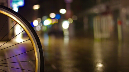 Closeup of a bicycle wheel in a rainy street at night