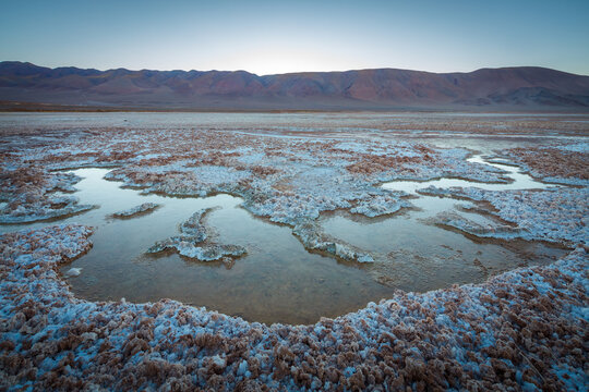 The salt plain Salina Tolar Grande in nortwest Argentina with small water filled puddles just before sunrise