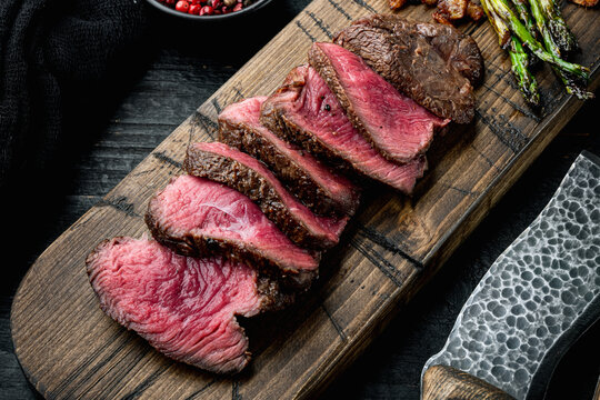 Sliced grilled marbled meat steak Filet Mignon, with onion and asparagus, on wooden serving board, with meat knife and fork, on black wooden table background