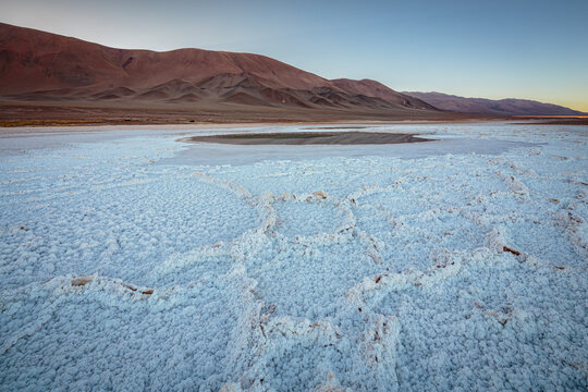 Landscape with polygonal salt structures on the salt flat Salina Tolar Grande and mountains in the blue hour before sunrise