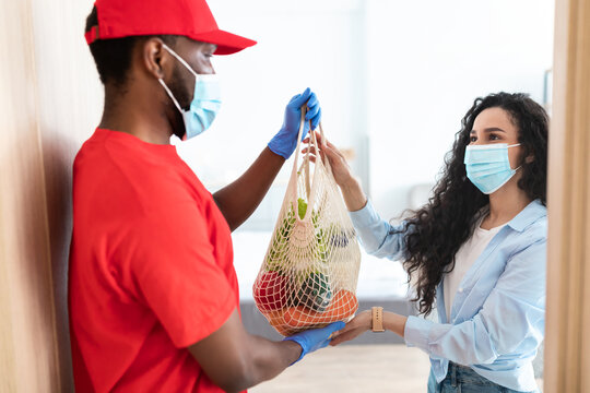 Black delivery man giving net mesh bag with groceries