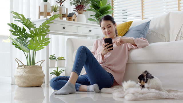 Young attractive beautiful asian lady wear earphone happy listen digital podcast online channel for reskill upskill mindfulness break at home in quarantine social distance self isolate on sofa couch.