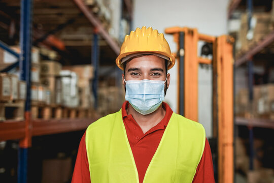 Man working inside warehouse while wearing surgical face mask - Industrial worker and safety measures for coronavirus outbreak