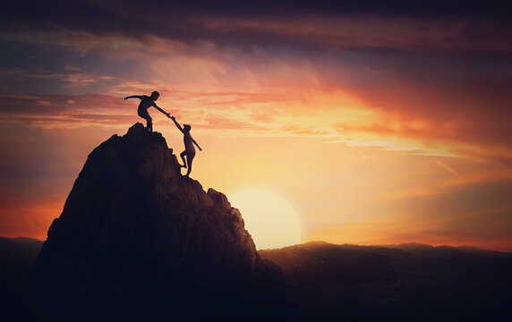 Scenery view with a team of two climbers on the top on the mountain. Person helping another to overcome obstacles and reach the top together. Teamwork concept, working in group to achieve success
