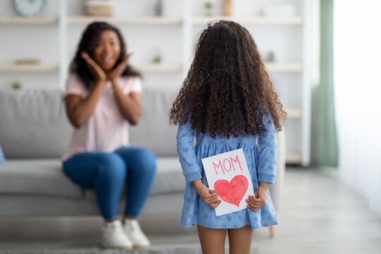 Cute black girl congratulating excited mother with holiday, hiding greeting card behind her back at home, copy space