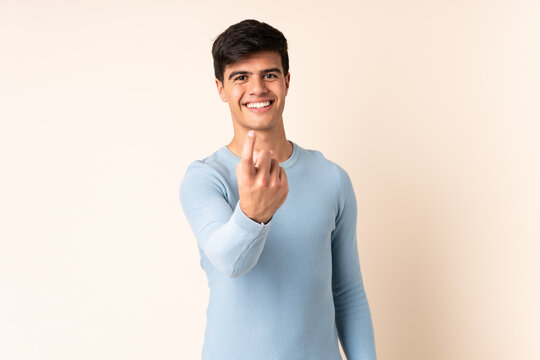 Handsome man over isolated beige background doing coming gesture