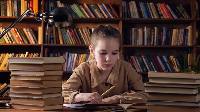 Tired young lady in brown jacket writes out information from textbook into copybook preparing to online classes under electric light in late evening
