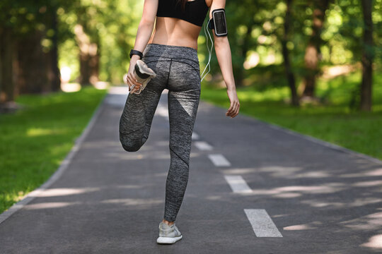 Unrecognizable female jogger preparing for run in city park, stretching leg muscles