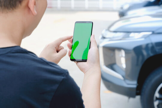 A Man standing next to the car. man using smartphone mockup green screen near the car. Mobile phone apps for car lock owners concept.