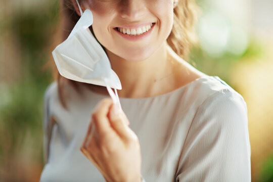 Smiling female in grey blouse taking off ffp2 mask