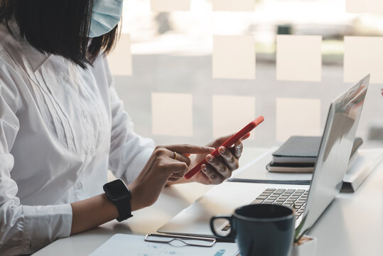 Image of a businesswoman wearing a mask to prevent germs playing with a mobile phone at the office.