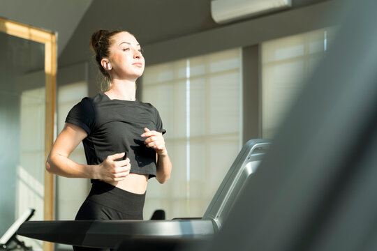 Concept fitness sport training lifestyle.Young woman running on a treadmill indoors. Young female running on the treadmill at their local gym.