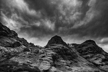 Obraz Majestic moody  black and white landscape image of Three Sisters in Glencoe in Scottish Highlands on a wet Winter day wit high water running down mountains - fototapety do salonu