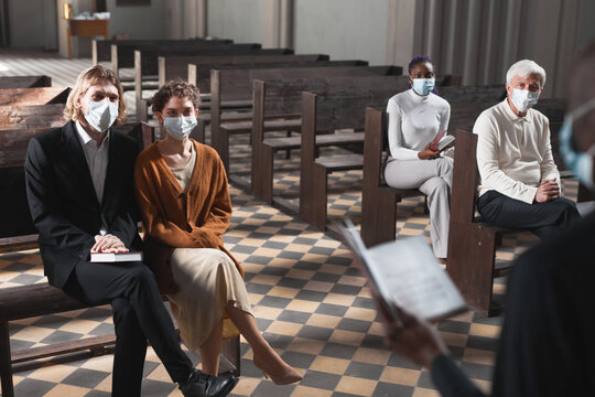 Group of people in protective masks sitting on bench and listening to mass in the church during pandemic