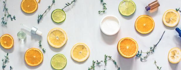 Fototapeta Natural citrus cosmetics with vitamin C, cosmetic bottles, citrus circles, lime, orange, lemon, top view, flat lay, copy space obraz