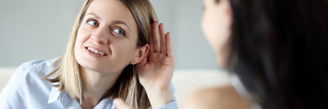Young woman holding her ear and talking to friend