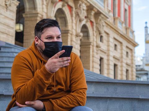 Hombre joven usando su móvil con mascarilla durante la pandemia del coronavirus