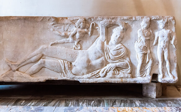 Sculpture carved on marble showing a naked roman man laying down on an ancient bed