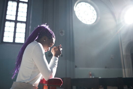 African young woman sitting in front of the altar in the church and praying