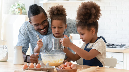 Happy dad teaching two cute preschooler kids to bake. Children and daddy beating eggs and sifting flour into bowl for kneading dough, making pie, cookies together. Family cooking, home bakery concept