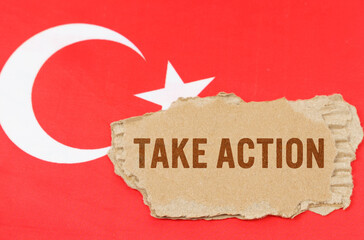 Against the background of the flag of Turkey lies cardboard with the inscription - Take Action