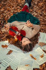 A beautiful girl lies with a violin on sheets with notes among the autumn orange foliage in the...