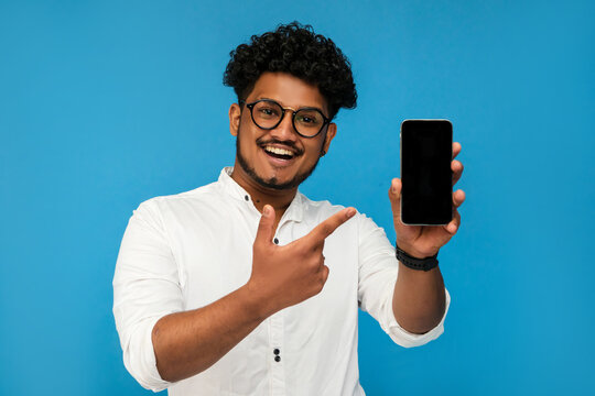 Portrait of a smiling handsome Indian guy, he holds a modern smartphone with a black screen in his hand and points to it with a bunch, a place for text. Copy space. blue background